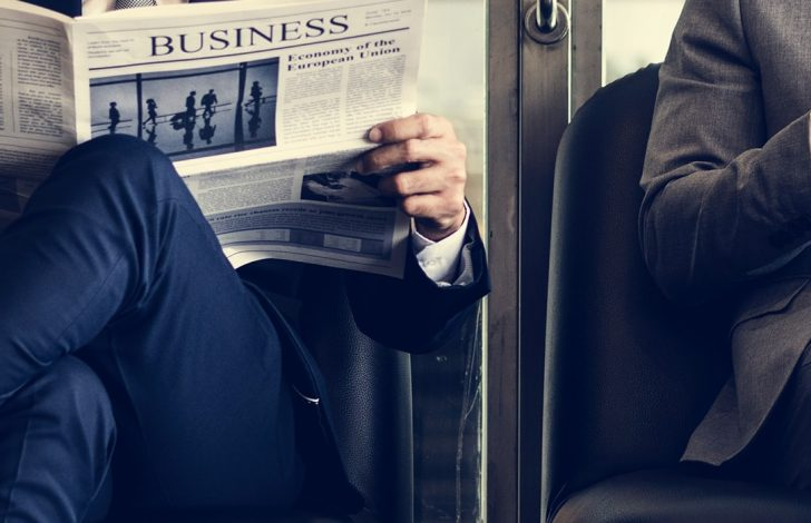 two business brokers sitting reading a business newspaper