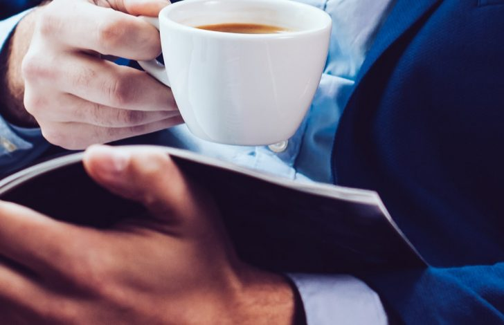 close up of business man drinking coffee and reading information